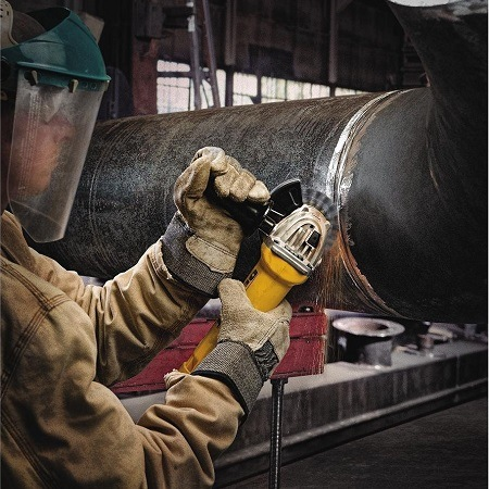 Man Cutting Pipe With DEWALT Angle Grinder