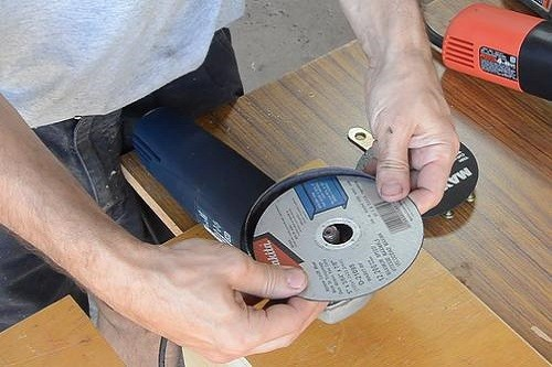Man Changing Abrasive Wheel On Angle Grinder
